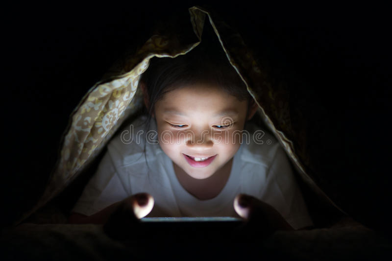 Bambino asiatico che per mezzo del PC della compressa a letto alla notte fotografie stock libere da diritti