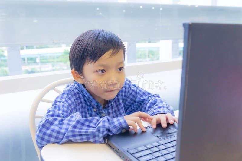 Bambino asiatico con il computer portatile fotografie stock