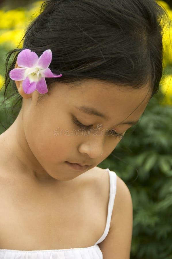 Bambino asiatico con il fiore in suoi capelli fotografie stock libere da diritti