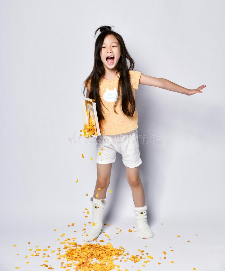 Bambino asiatico dai capelli lunghi della ragazza in vestiti domestici che canta gridando di mattina i fiocchi di mais di poures  immagine stock libera da diritti