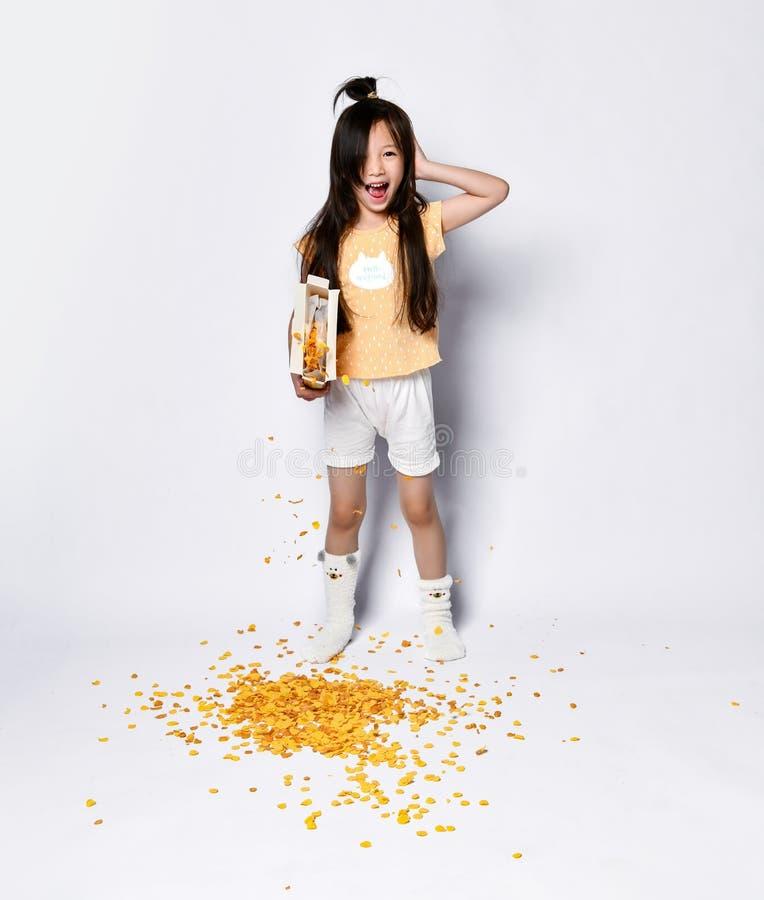 Bambino asiatico della ragazza di imbardata venuto a mancare con produrre prima colazione alla mattina Lei che versa fuori i fioc fotografie stock