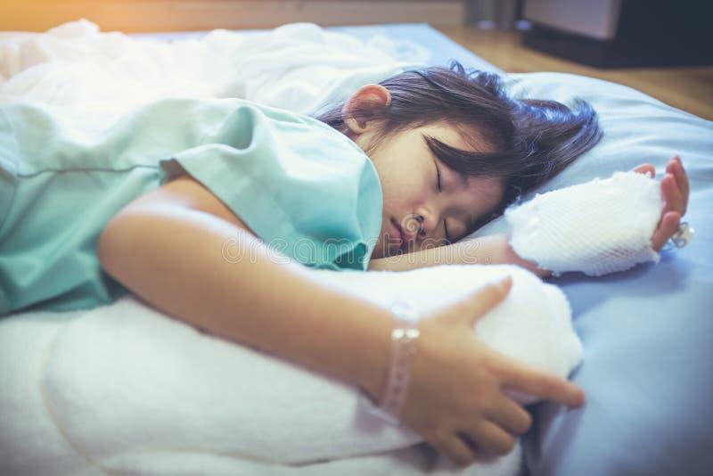Bambino asiatico di malattia ammesso in ospedale con il gocciolamento salino del dispositivo di venipunzione sopra fotografia stock