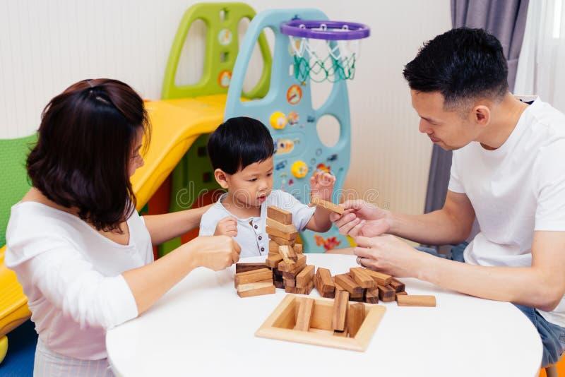 Bambino asiatico e genitori che giocano con i blocchi di legno nella stanza a casa Un genere di giocattoli educativi per la scuol immagine stock