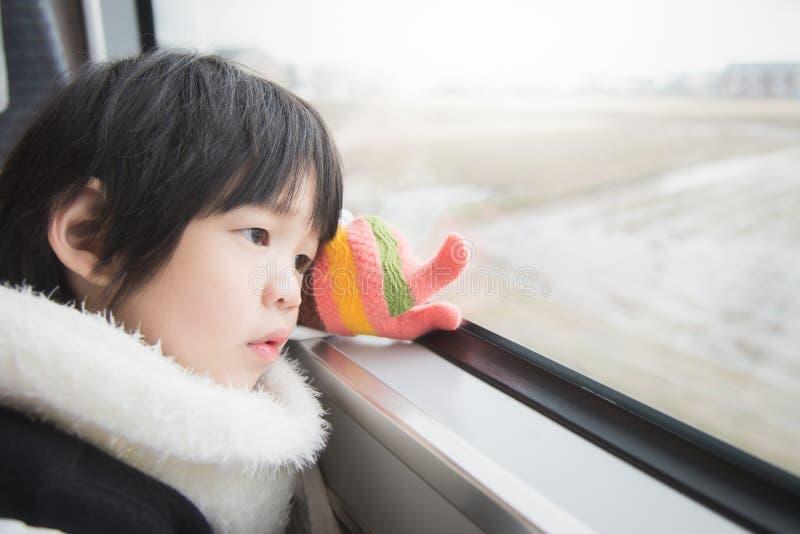 Bambino asiatico felice che guarda fuori la finestra del treno fuori immagini stock libere da diritti