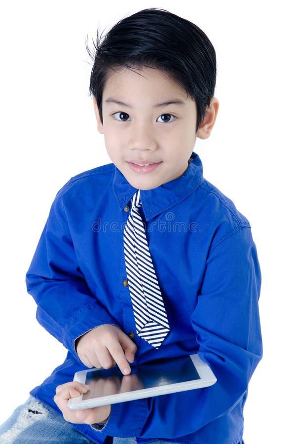Bambino asiatico felice con il computer della compressa su fondo isolato fotografia stock