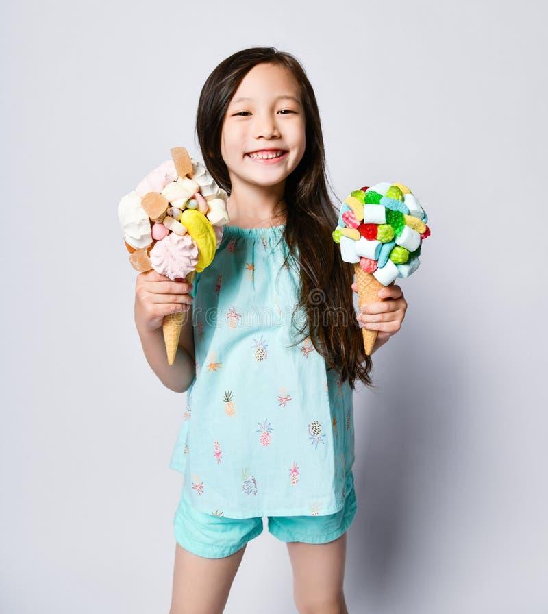 Bambino asiatico sorridente felice della neonata con due grandi gelati nei coni delle cialde con le guarnizioni saporite immagini stock