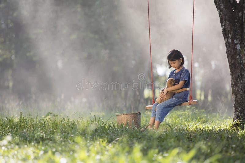 Bambino asiatico su oscillazione con il cucciolo fotografia stock