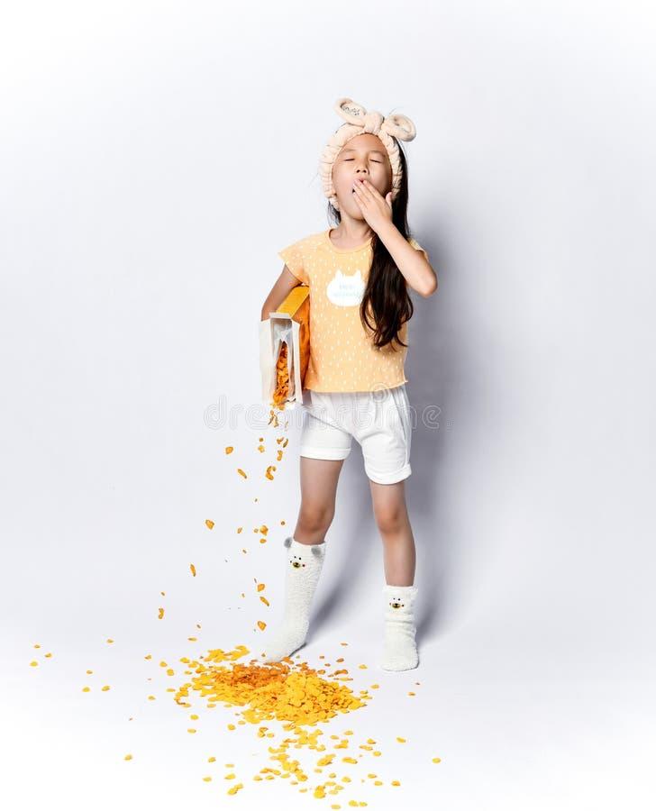 Bambino asiatico svegliato della ragazza del bambino in vestiti domestici alla prima colazione di mattina che versa fuori i fiocc fotografia stock libera da diritti
