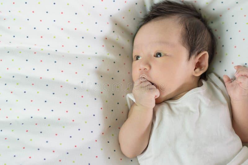 Bambino asiatico sveglio che mette su letto fotografia stock libera da diritti