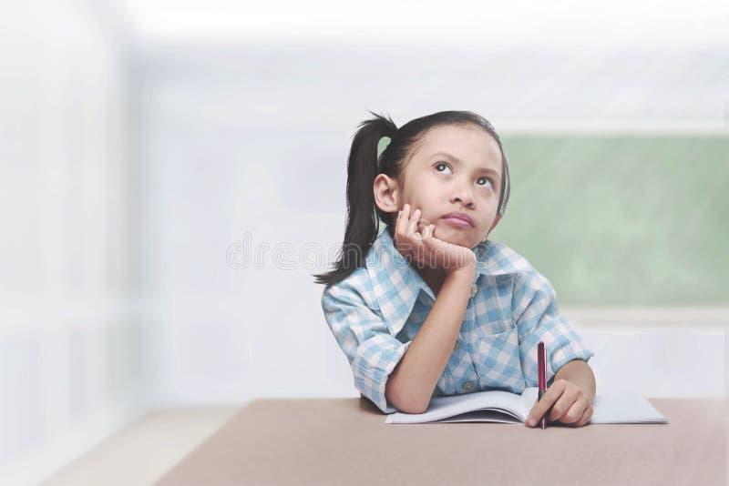Bambino asiatico sveglio con l'apprendimento della penna e del libro immagine stock