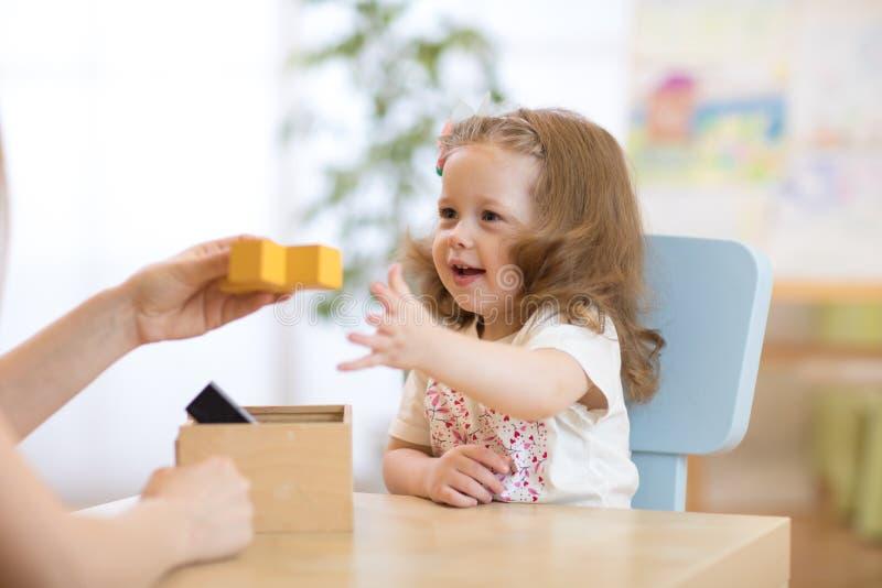 Bambino astuto con i giocattoli didattici in scuola materna fotografia stock libera da diritti
