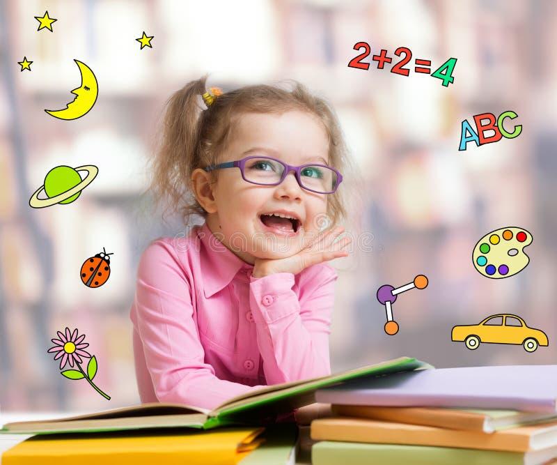 Bambino astuto divertente in libro di lettura di vetro immagine stock libera da diritti