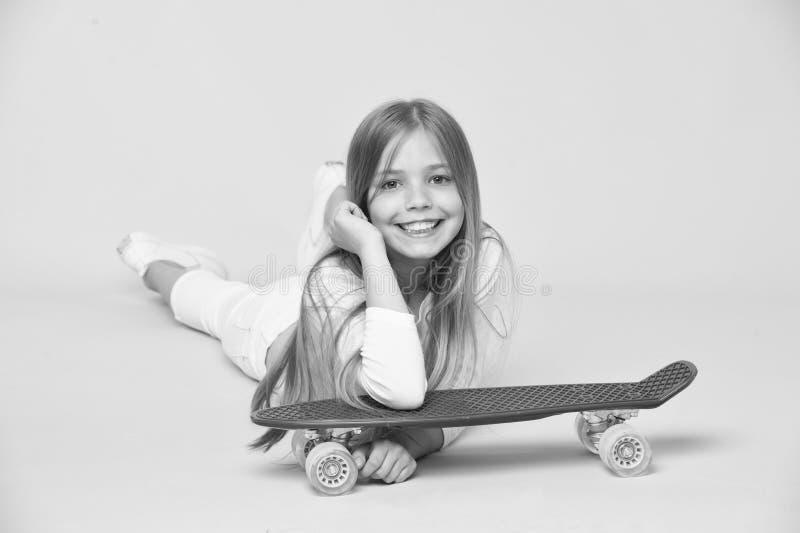 Bambino in attrezzatura bianca che si trova sul pavimento Ragazza con capelli biondi lunghi isolati su fondo rosa Bambino con la  immagini stock libere da diritti