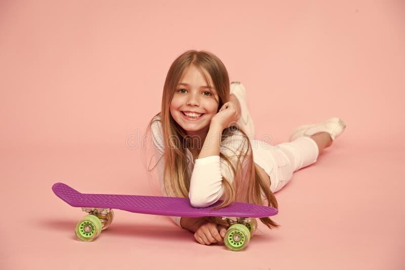 Bambino in attrezzatura bianca che si trova sul pavimento Ragazza con capelli biondi lunghi su fondo rosa Bambino con la tendenza fotografia stock libera da diritti