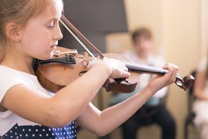 Bambino, bambina che gioca violino all'interno nella classe di musica fotografia stock