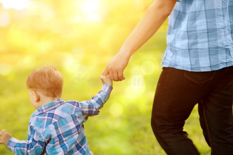 Bambino, bambino che tiene una mano adulta del ` s Padre e figlio su una camminata T immagine stock libera da diritti