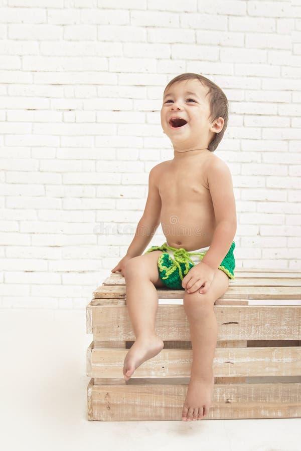 Bambino bello sveglio che ride mentre sedendosi sulla scatola di legno immagine stock