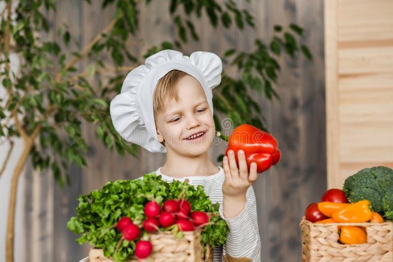 Bambino bello in uniforme del cuoco unico con le verdure Cucinando nella cucina a casa vegetariano Alimento sano fotografia stock