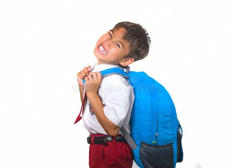 Bambino in borsa di trasporto uniforme in pieno dei libri che ritengono ribaltamento e che protestano circa il peso dello zaino n immagini stock