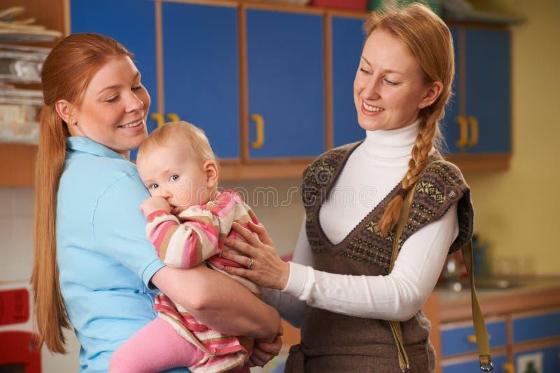 Bambino cadente della madre di funzionamento alla scuola materna immagine stock libera da diritti