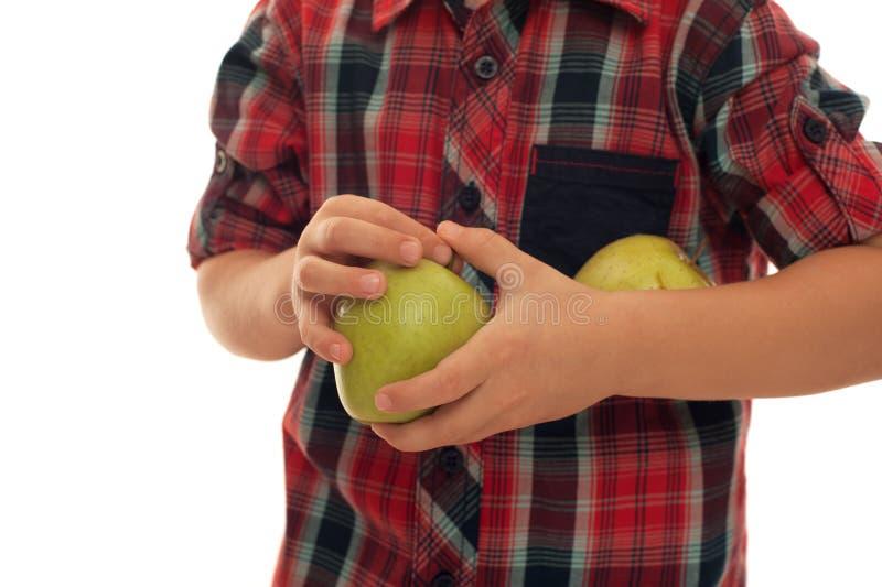 Bambino in camicia rossa che tiene due mele verdi fresche immagini stock