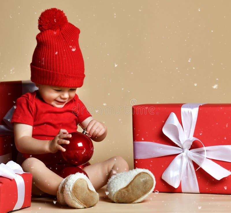 Bambino in cappello rosso con le pile di scatole attuali intorno alla seduta sul pavimento immagini stock libere da diritti