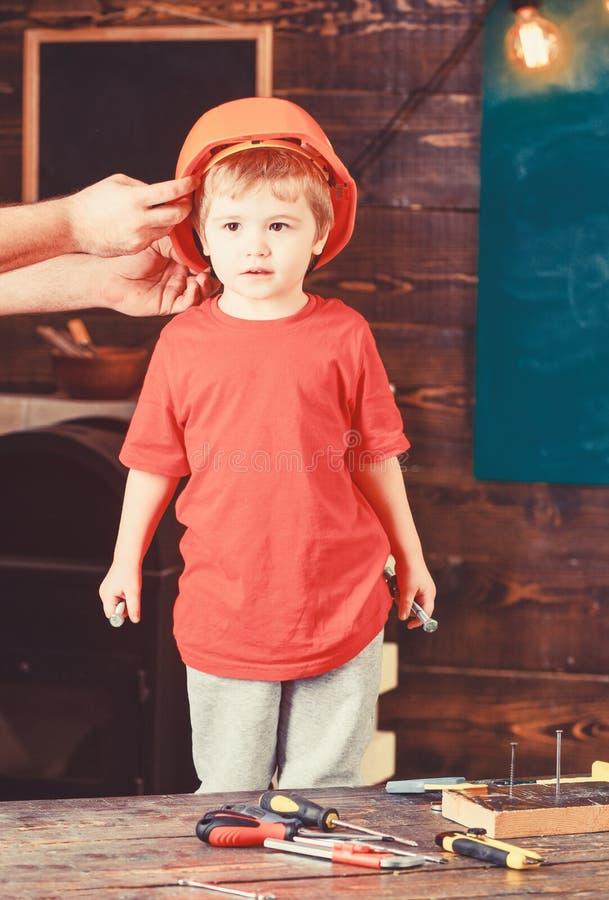 Bambino in casco protettivo, casco a casa in officina Supporti svegli ed adorabili del bambino mentre mani maschii che mettono du immagine stock libera da diritti
