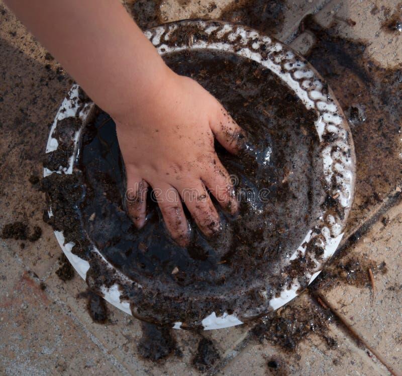 Bambino che produce una torta del fango immagine stock