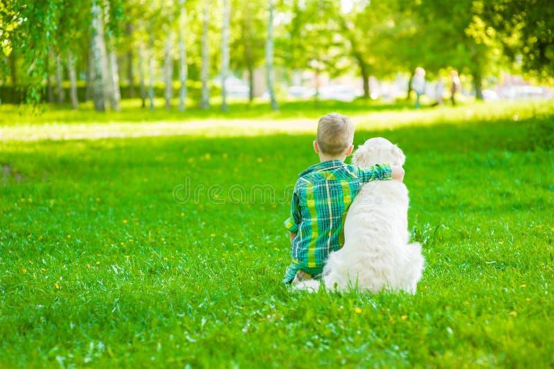 Bambino che abbraccia golden retriever, sedentesi con il suo di nuovo alla macchina fotografica fotografia stock libera da diritti