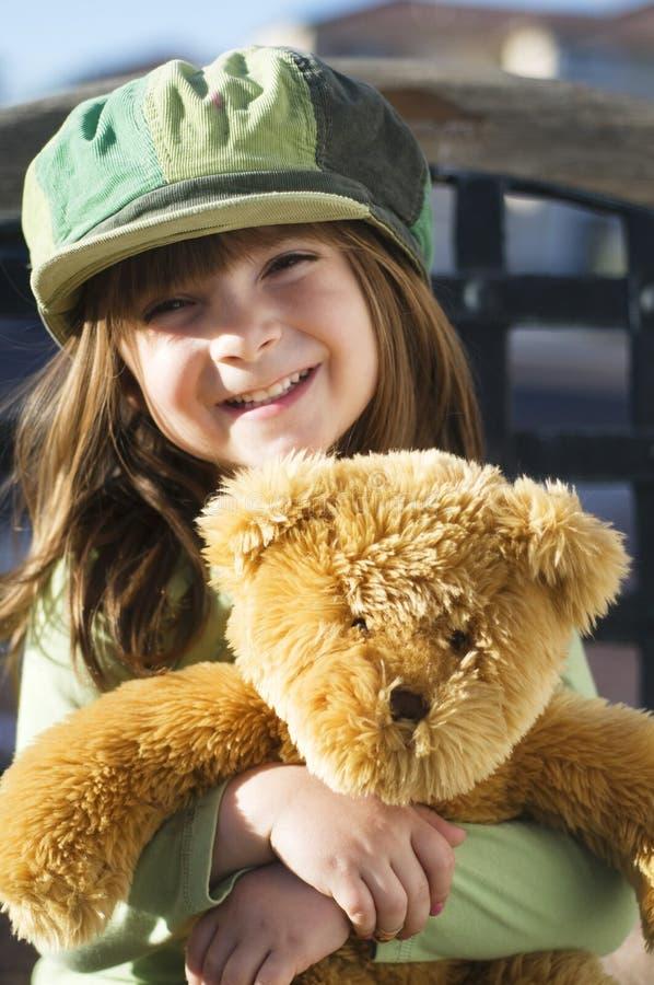 Bambino che abbraccia il suo orso di orsacchiotto immagini stock libere da diritti