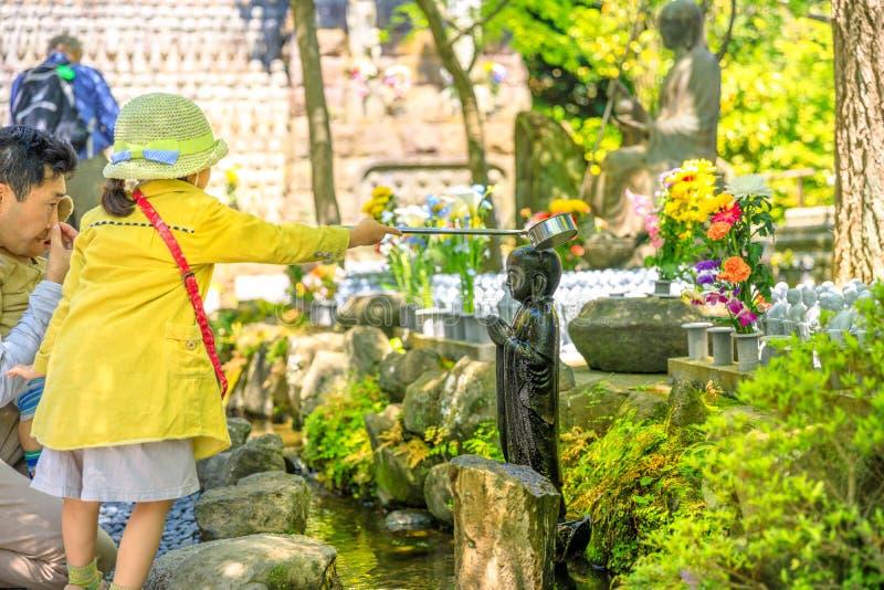 Bambino che adora la statua di Jizo immagine stock libera da diritti