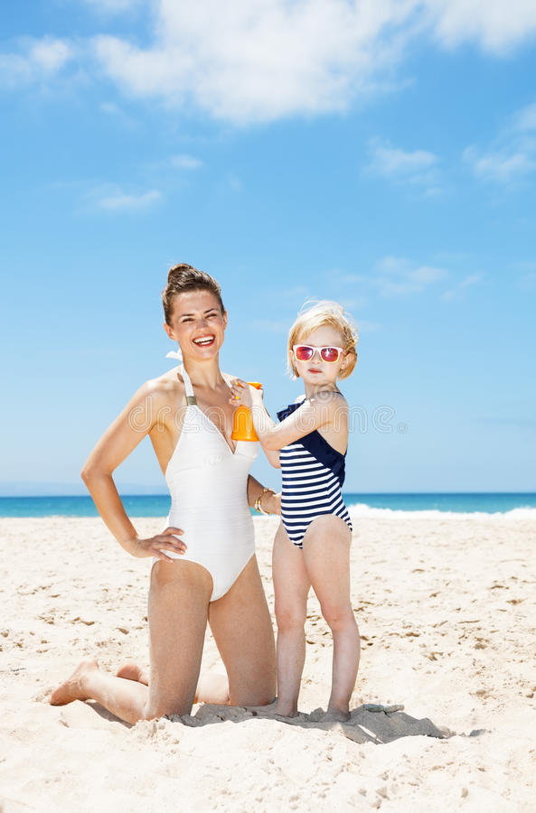 Bambino che applica protezione solare sulla madre sorridente in costume da bagno alla spiaggia immagini stock libere da diritti