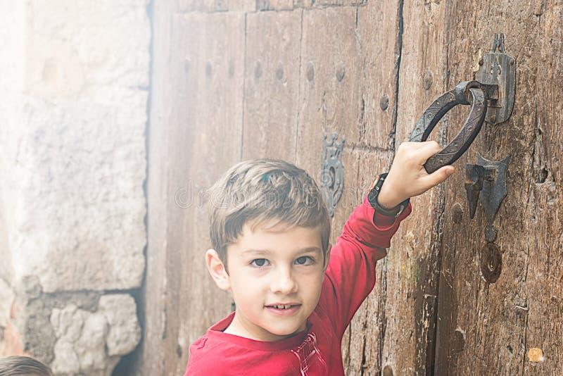 Bambino che batte su una vecchia porta immagini stock