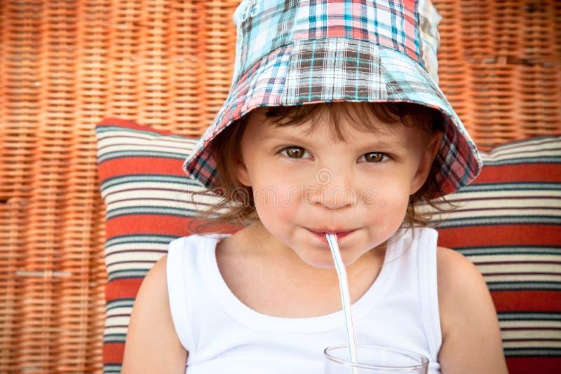 Bambino che beve attraverso una paglia immagini stock libere da diritti