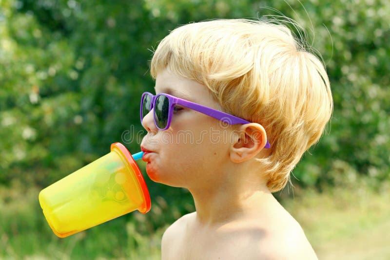 Bambino che beve il giorno di estate caldo immagini stock