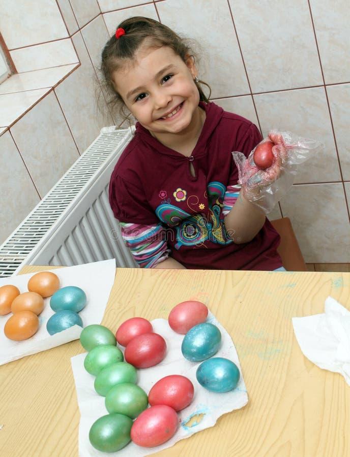 Bambino che colora le uova di Pasqua immagini stock libere da diritti