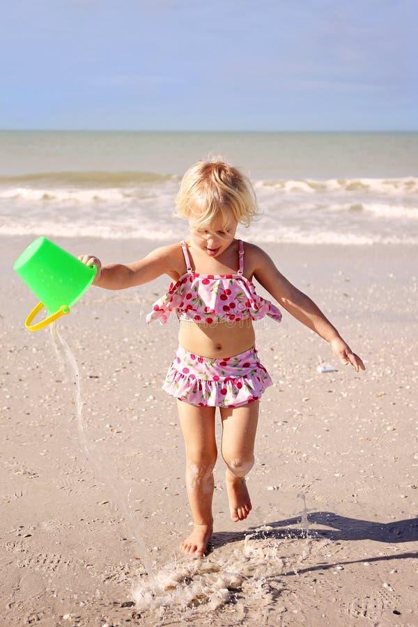 Bambino che corre sulla spiaggia dall'oceano con un secchio di acqua fotografia stock