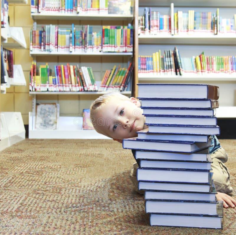 Bambino che dà una occhiata dietro una pila di libri alla biblioteca fotografia stock