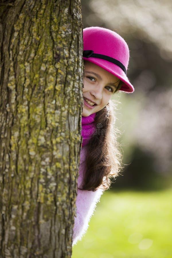 Bambino che dà una occhiata dietro un albero fotografia stock libera da diritti