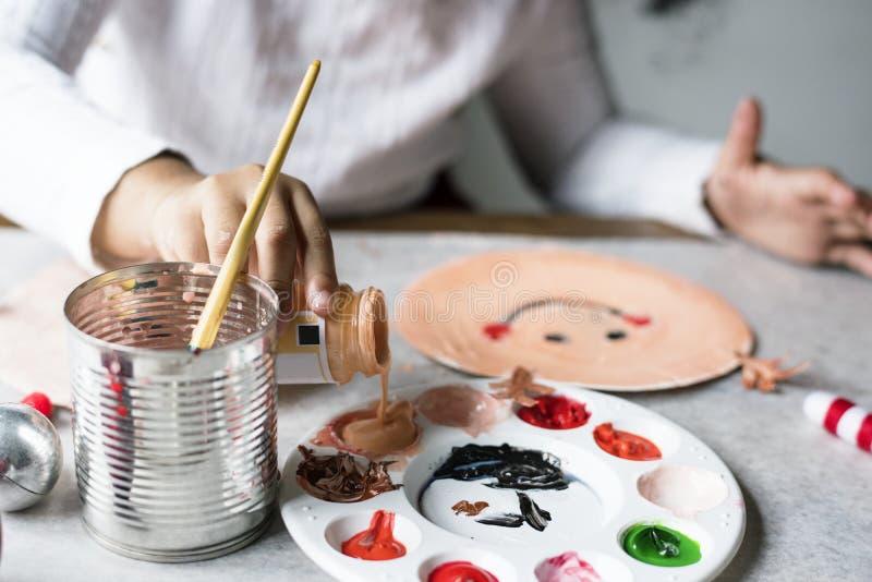 Bambino che dipinge Santa su un piatto di carta immagini stock libere da diritti