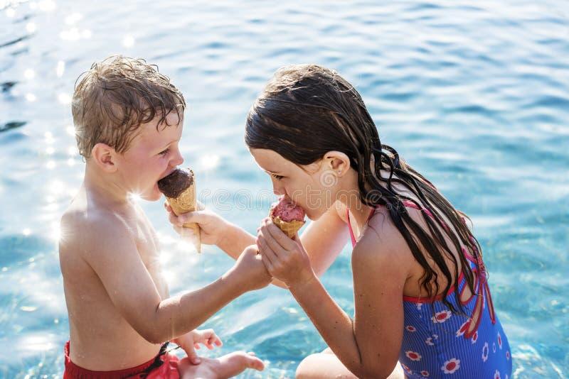 Bambino che divide un gelato dallo stagno immagini stock