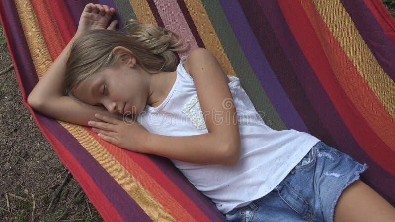 Bambino che dorme in amaca nel campeggio, bambino che si rilassa nella foresta, ragazza in montagne fotografia stock libera da diritti