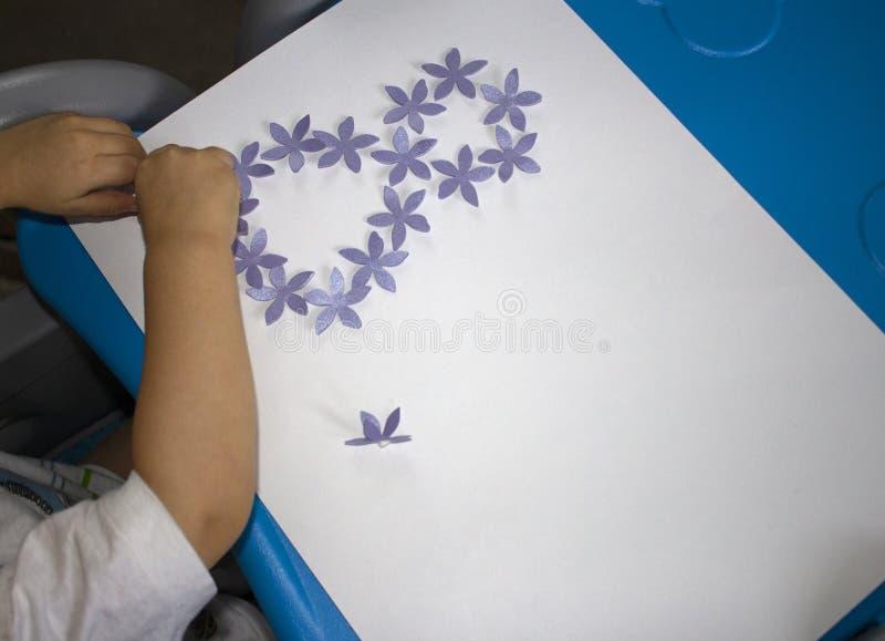 Bambino che fa cartolina con immagine l'8 marzo Lavoro di ufficio del bambino Materiale per creatività asilo fotografia stock