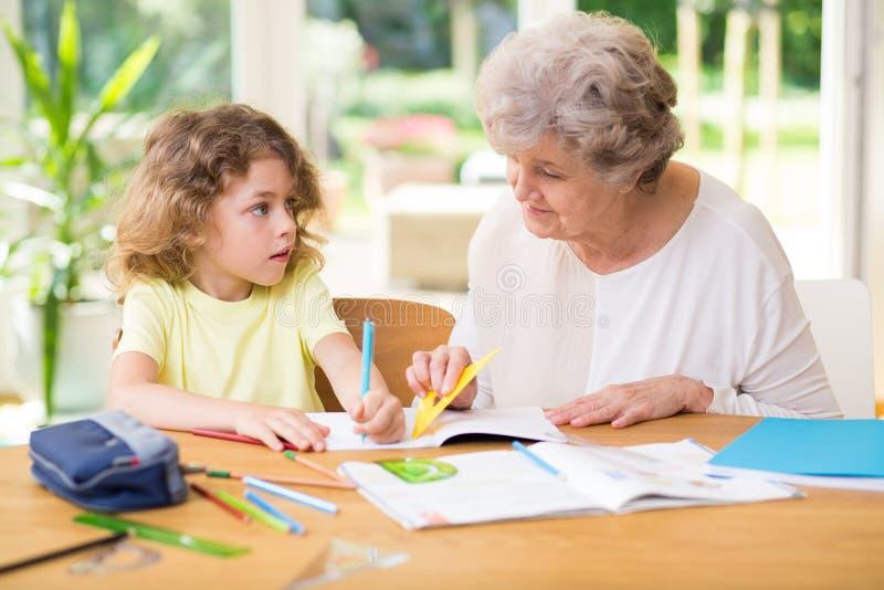 Bambino che fa compito con sua nonna immagine stock