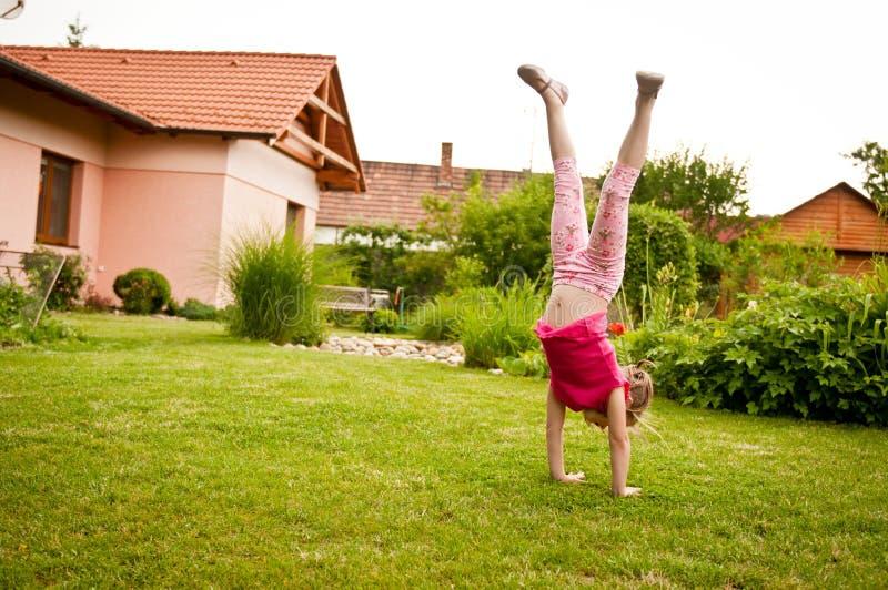 Bambino che fa handstand in cortile fotografie stock