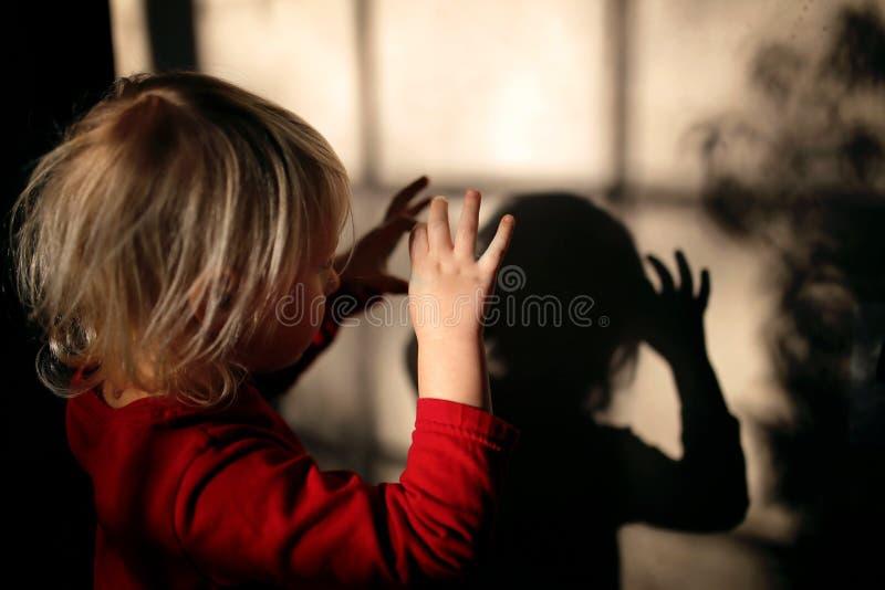 Bambino che fa i burattini dell'ombra con le dita sulla parete della sua casa fotografia stock libera da diritti