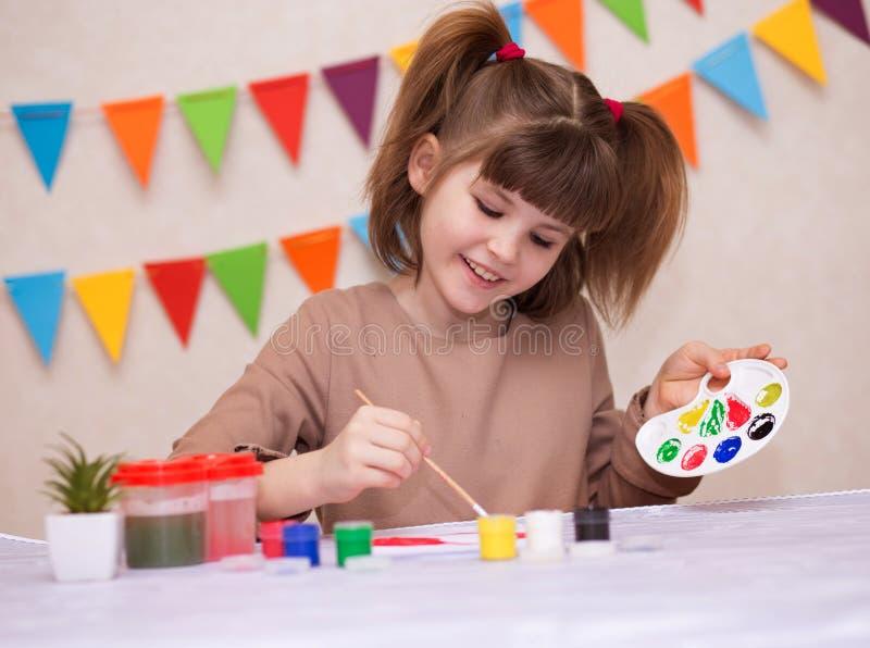 Bambino che fa la cartolina d'auguri casalinga La bambina dipinge il cuore sulla cartolina d'auguri casalinga come regalo per il  immagine stock libera da diritti