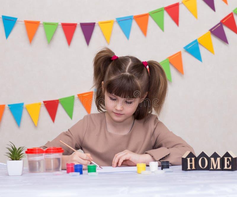 Bambino che fa la cartolina d'auguri casalinga La bambina dipinge il cuore sulla cartolina d'auguri casalinga come regalo per il  fotografie stock