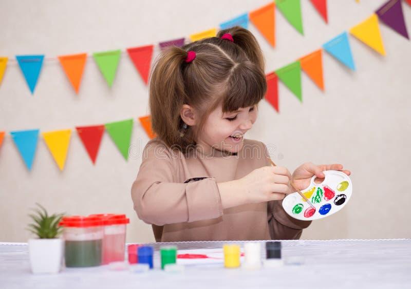 Bambino che fa la cartolina d'auguri casalinga La bambina dipinge il cuore sulla cartolina d'auguri casalinga come regalo per il  immagini stock