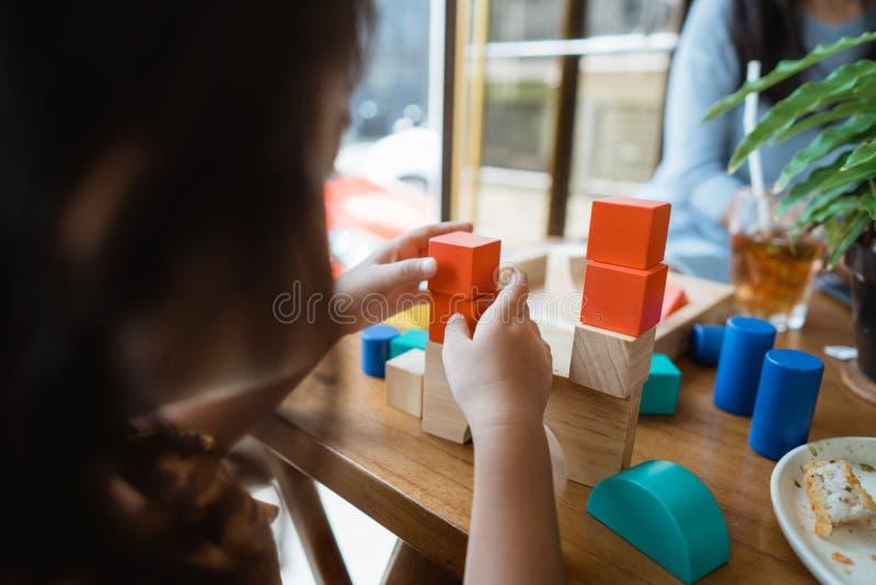 Bambino che fa un'alta torre dal blocco di legno fotografia stock libera da diritti